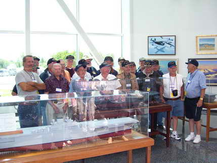 Crew of the Kalinin Bay at their ship's model at the Air Museum